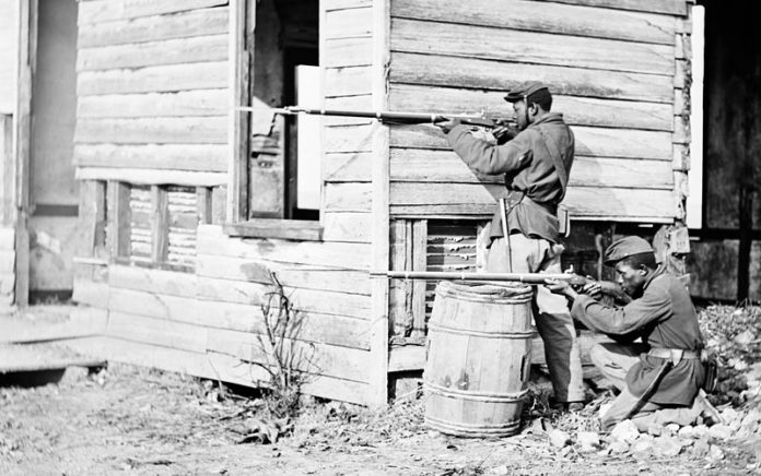 Black soldier fought in the Civil War - in position behind a house with rifles near Dutch Gap Virginia